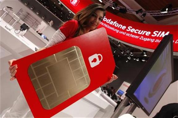 A staff member poses with a mock oversized Vodafone Secure SIM card at the Vodafone booth at the CeBit computer fair in Hanover, March, 5, 2012. REUTERS/Fabrizio Bensch/Files